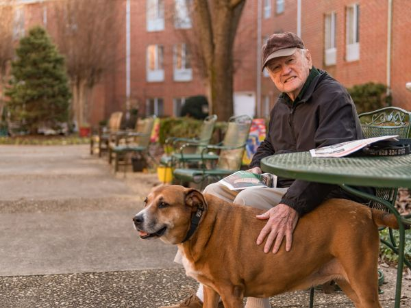 Resident & Dog Enjoying Outdoor Courtyard | Kingston in Hickory